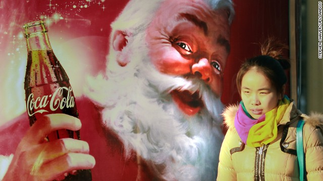 A girl walks by a Coca-Cola Christmas ad in Beijing on December 19.