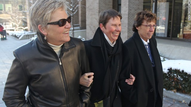 Plaintiffs Laurie Wood, left, and Kody Partridge, center, and their attorney Peggy Tomsic leave a federal courthouse in Salt Lake City on Wednesday, December 4, where a judge heard arguments challenging Utah's same-sex marriage ban.