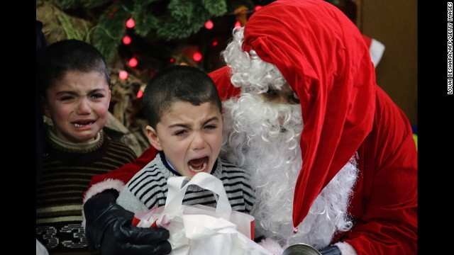 Boys cry as they are pictured with Santa Claus at a kindergarten in Damascus, Syria, on December 19.