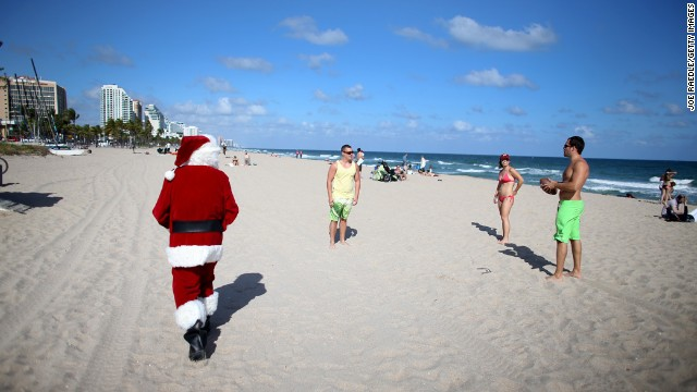 Tom Tapp dressed as Santa Claus walks along the beach passing out candy canes and posing for pictures with beachgoers on December 20, in Fort Lauderdale, Florida.