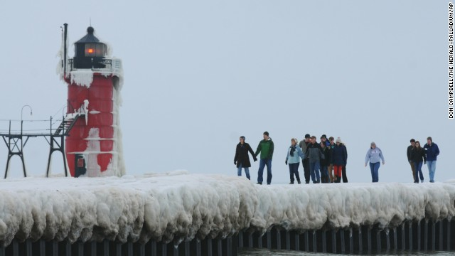 People walk along an ice-covered pier near the South Haven Lighthouse on December 21 in South Haven, Michigan.