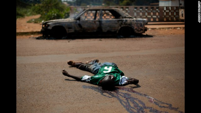 The body of a suspected militiaman lies in the road near a charred car in Bangui on Friday, December 20.