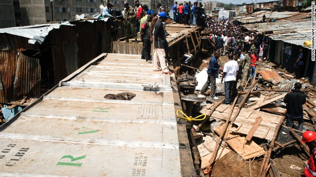 People stand on a cargo train after it derailed in the sprawling Nairobi slum of Kibera.