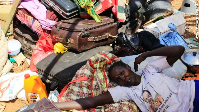 A mother displaced by recent fighting in South Sudan rests on top of her belongings inside a makeshift shelter at the United Nations Mission in Sudan on Monday, December 23. Clashes between rival groups of soldiers in the capital of Juba a week ago have spread across the country.
