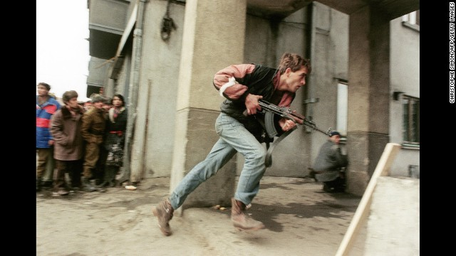 An anti-Communist civilian fighter runs with an AK-47 during a street-fight in Bucharest, Romania, in 1989.