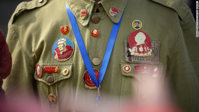 A man displays badges of Mao Zedong.