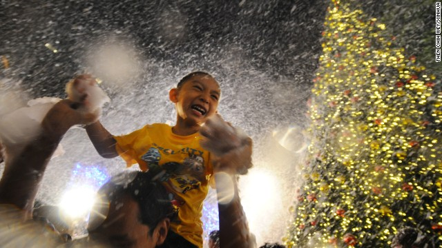 A child enjoys artificial snow at a shopping mall in Singapore on Tuesday, December 24.