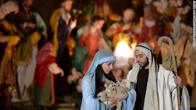 People act out a nativity scene during the unveiling ceremony of the crib in St. Peter's Square at the Vatican on December 24.
