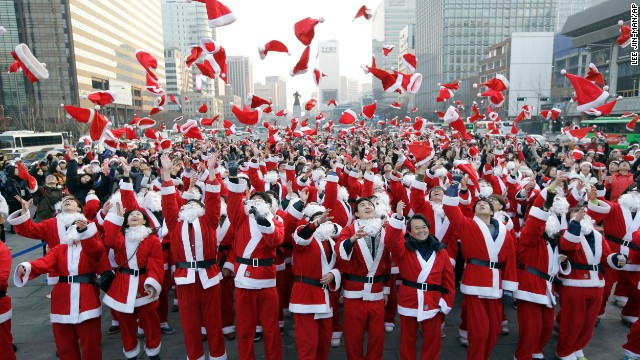 More than 1,000 volunteers clad in Santa Claus costumes throw their hats in the air as they gather to deliver gifts for the poor in downtown Seoul, South Korea, on December 24.