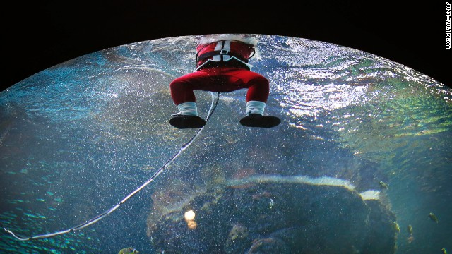 A diver dressed as Santa Claus surfaces after swimming in the Coral Garden tank at the South East Asia Aquarium of Resorts World Sentosa, a popular tourist attraction in Singapore, on December 24.