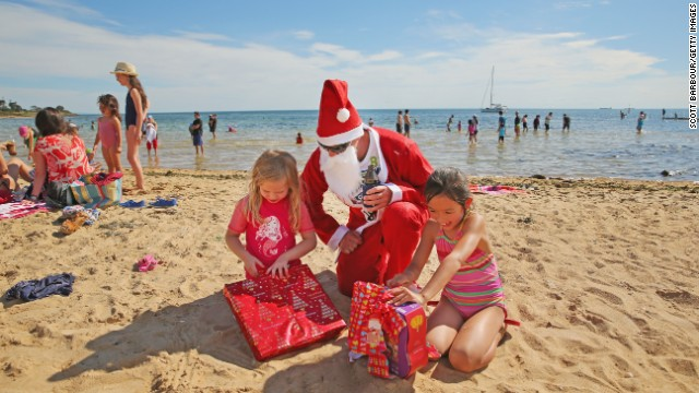 A man dressed as Santa Claus helps children open presents at Brighton Beach in Melbourne, Australia.