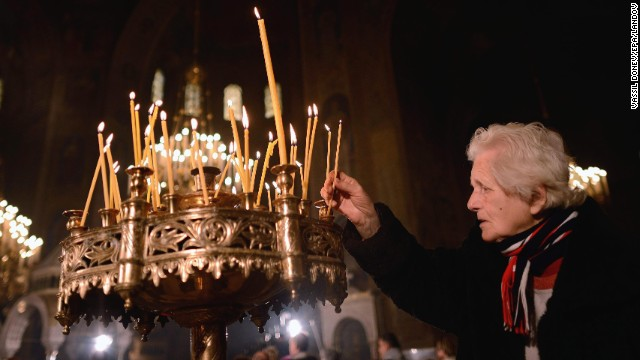 A woman lights a candle during a Christmas Day Mass in Sofia, Bulgaria.