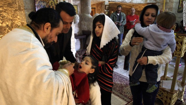 A priest blesses a child during a morning Mass in the West Bank village of Burqin near Jenin.