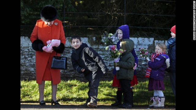 Great Britain's Queen Elizabeth II receives gifts from children following a service at St. Mary Magdalene Church on the royal estate in Sandringham, England.