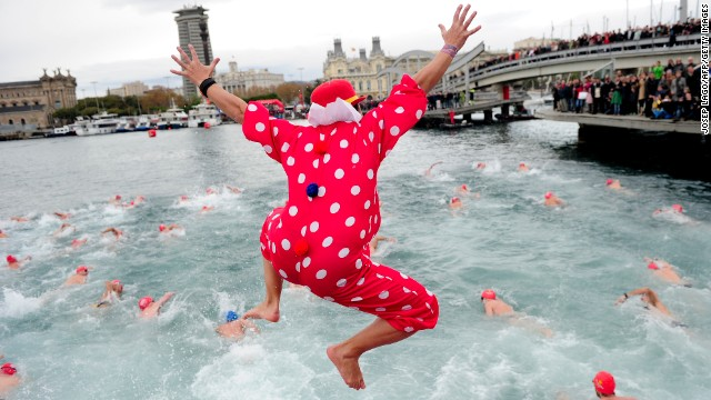 A participant in the Copa Nadal, or Christmas Cup, jumps into the waters of Port Vell in Barcelona, Spain.