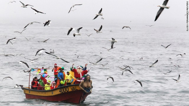 Ruben Torres, dressed in a Santa Claus outfit, waves to people from a boat with fishermen along the coast of Valparaiso, Chile, on December 24. Every year, fishermen in Valparaiso organize a Santa Claus boat trip as people wait on the shore to receive their Christmas presents and well-wishes.