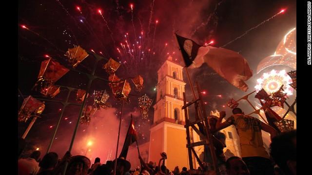 People launch fireworks during the traditional celebrations of Parrandas de Remedios in Villa Clara, San Juan de los Remedios, Cuba. Parrandas, the oldest celebration of Cuba, was declared a national heritage this year.