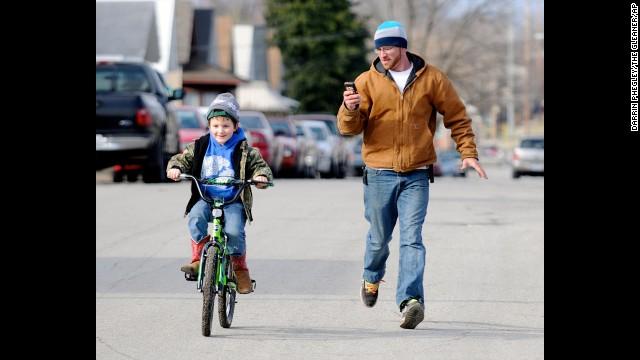 Levi Marez runs alongside his son Kaden Fletcher, 6, left, as he learns to ride the bike he got for Christmas in Henderson, Kentucky.