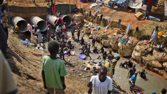 Displaced people bathe and wash clothes in a stream in a U.N. compound in Juba on December 27.