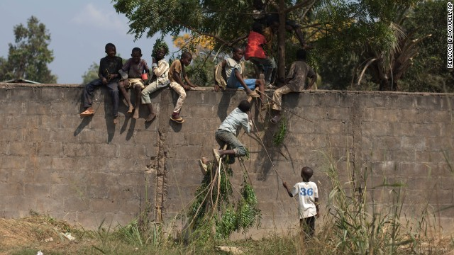 Displaced young people use a tree branch to climb a wall in Bangui on Saturday, December 28.