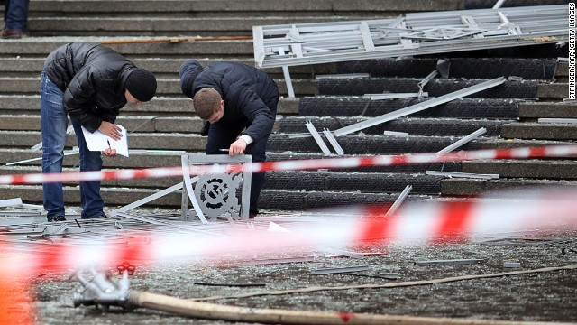 Police investigators inspect debris at the scene of the explosion.