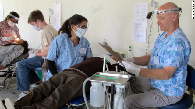 CNN reporter Moni Basu, center, helps pediatric dentist Raymond Broussard, right, at the clinic. The hours were long, but satisfying, she said.