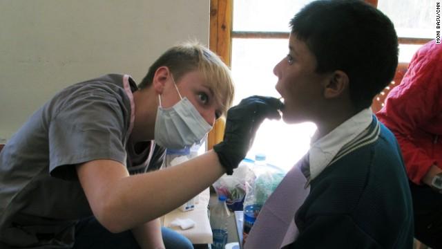 Larkin Broussard, left, applies fluoride to a boy's teeth at the makeshift dental clinic in Leh.