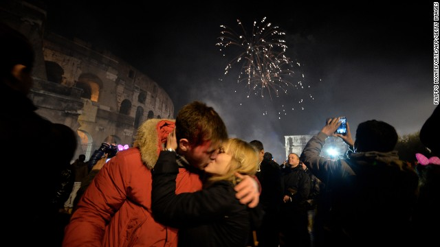 A couple kisses by the ancient Coliseum to celebrate the new year in Rome.