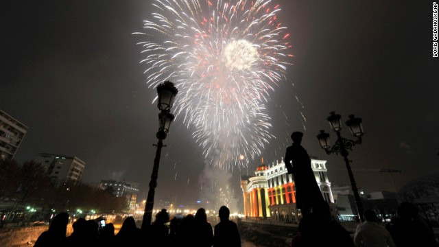 People watch fireworks explode over the Vardar River during New Year's celebrations in Skopje, Macedonia.