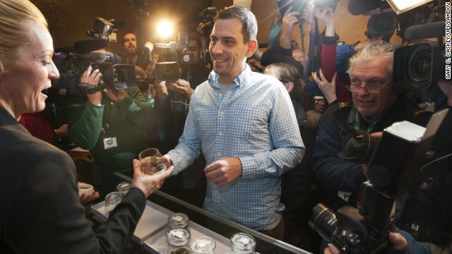 "Sean Azzariti, an Iraq war veteran and marijuana activist, speaks to the media Wednesday, January 1, after becoming the first person to legally purchase recreational marijuana in Colorado. Colorado is the first state in the nation to allow retail pot shops. ""It's huge,"" Azzariti said. ""It hasn't even sunk in how big this is yet."""