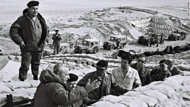 Former Prime Minister David Ben-Gurion is briefed in 1971 by Sharon in a trench near the Suez Canal in the Sinai.
