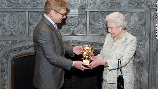 In recognition of a lifetime's support to British film and television, Queen Elizabeth receives an honorary BAFTA from actor Kenneth Branagh at Windsor Castle on April 4, 2013.
