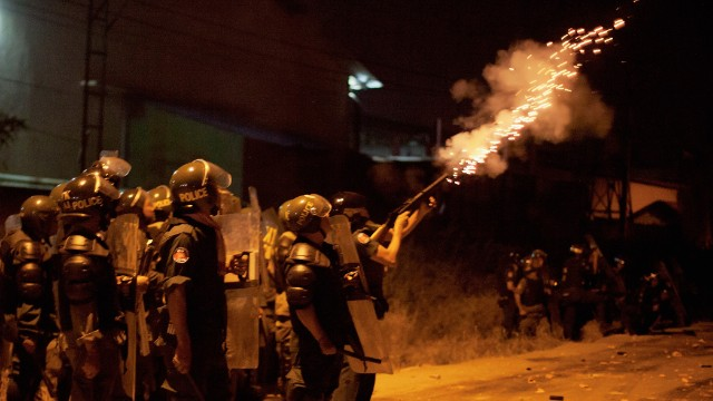 A member of the Cambodian police fires tear gas during a crackdown on striking garment workers on January 2 in Phnom Penh.