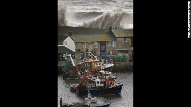 Waves break over the Cobb sea wall on January 3 in Dorset.