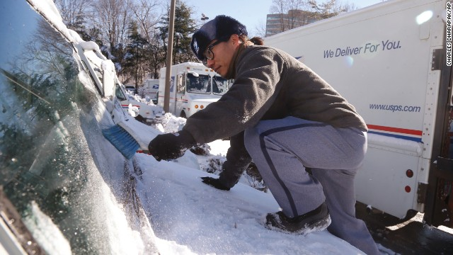 Postal worker Danny Kim clears snow and ice off the hood of his delivery truck January 3 in Bethesda, Maryland.