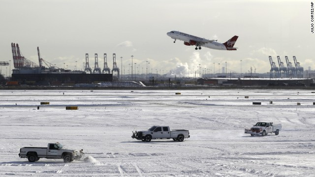 A plane takes off January 3 as trucks plow snow at Newark Liberty International Airport in Newark, New Jersey.