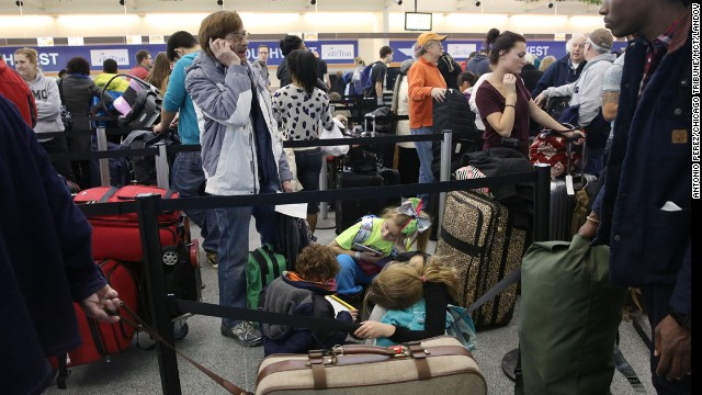 Travelers wait in line January 3 at Chicago Midway International Airport.