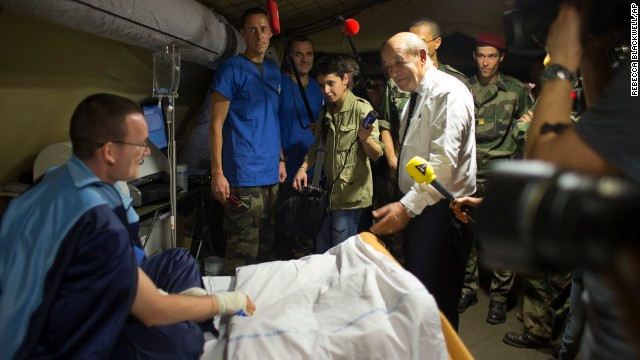French Defense Minister Jean-Yves Le Drian, center right, speaks to a wounded soldier in a medical tent during a visit to the M'Poko Camp in Bangui on Thursday, January 2. France has sent 1,600 troops into the Central African Republic to assist African troops.