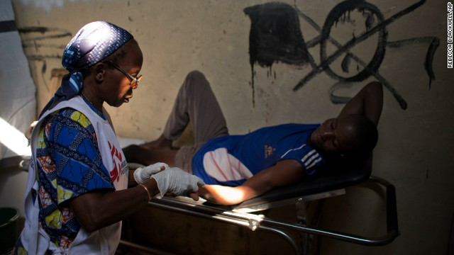 A medical worker checks the injuries of a man who has been struck by gunfire. The man was treated at a Doctors Without Borders clinic inside a makeshift camp in Bangui on January 2.