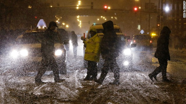 Basketball fans brave the cold and snow as they cross to the United Center in Chicago on Saturday, January 4.