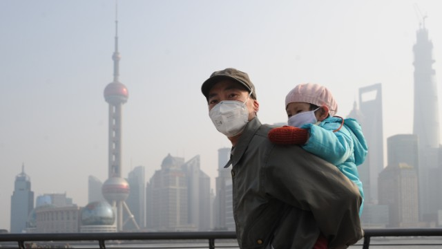 A man and his child wear masks as they visit Shanghai's Bund on December 25.