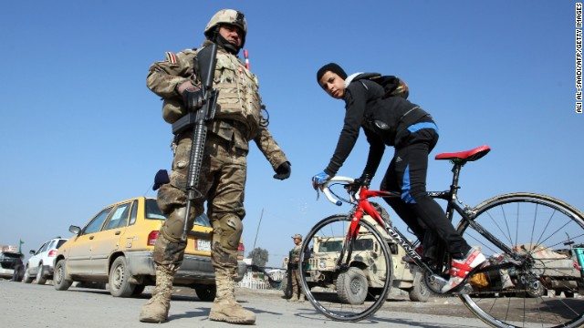 A boy cycles past Iraqi soldiers monitoring a checkpoint east of Baghdad on January 6, 2014.