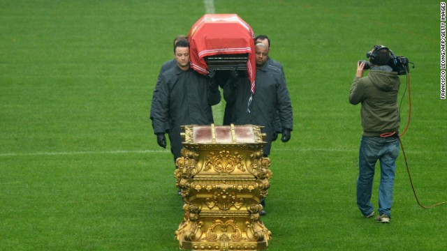 The coffin bearers place Eusebio's body down on a gold stand on the halfway line. The funeral takes place later Monday.