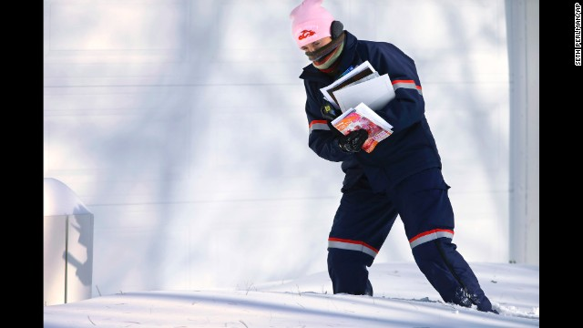 Postal worker Jamie Jasmon struggles to deliver mail in the snow January 6 in Springfield, Illinois.
