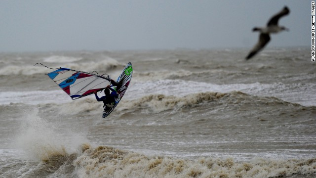 Off English shores, a windsurfer braves the elements. Gale force winds and a tidal surge caused widespread flooding in coastal areas of England and Wales.