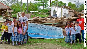 Fr. Berhabe Tujaha (left) with some of the pupils of St. Mary\'s elementary school, which was destroyed by Typhoon Haiyan.