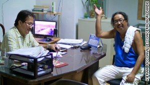 Leo Ladaquin waves a greeting from the mayor\'s office in Concepcion. On the left is Mayor Villanueva.