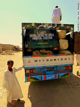 Struggling with barren sandy roads, the tuk tuk is loaded onto a truck in Sudan.