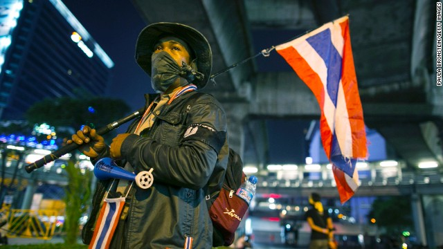 A volunteer security guard stands at one of the anti-government People's Democratic Reform Committee (PDRC) intersections that was shut down in early evening, blocking a major shopping district on January 12, 2014.