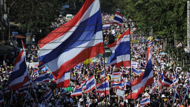 "Thai anti-government protesters wave national flags as they march through the streets of Bangkok in a move to ""shut down"" the city on January 13, 2014."